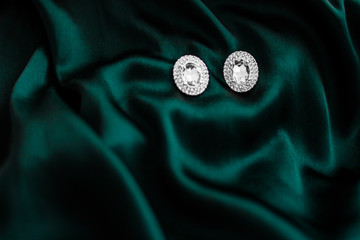 Luxury diamond earrings on dark emerald green silk, holiday glamour jewelery present
