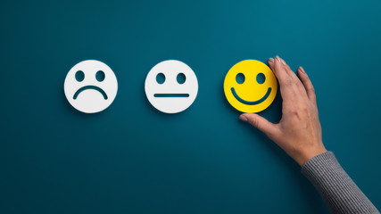 Woman choosing happy smiley face emotion on green Fototapete