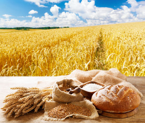 bread with wheat ears, grains and flour on wooden table on wheat field background