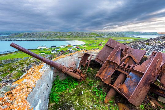 Old destroyed cannon in Hamningberg fort, German military vestige of 2d World War pastime. The abandoned fishers' village Hamningberg and the shore of the Barents Sea are at Background. Norway.