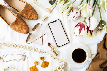 Fashion / beauty blogger home office desk. Blank screen smart phone, tulip flowers bouquet, clothes...
