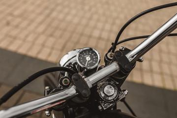 Round vintage speedometer on a motorcycle steering wheel - chrome detail in vintage style
