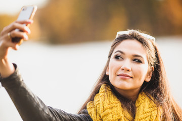 Selfie on a smartphone - beautiful cheerful brunette girl is photographed