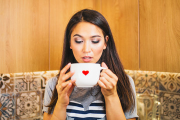 White mug with a hot drink and a red heart on its side