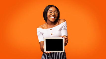 Afro Girl Showing Digital Tablet Screen Standing In Studio, Panorama