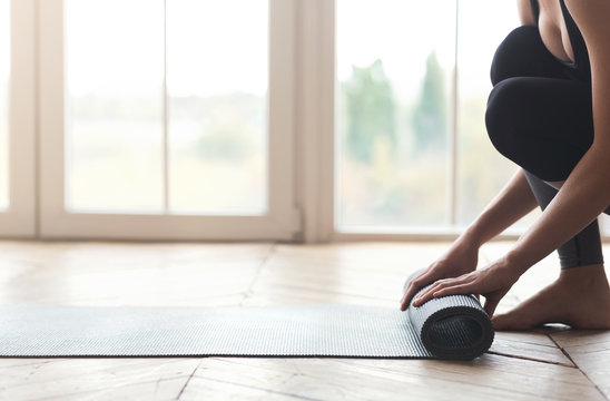 Side view of woman rolling her yoga mat before training