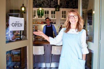 Small business owner woman standing in cafe door and smiling