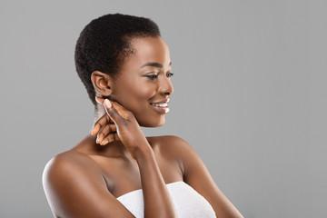 Fototapete - Beautiful african woman enjoying her soft skin on cheek