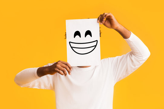 African american man holding paper with smiley face