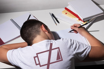 Bored and tired boy doing homework on white desk in his room. Schoolboy probems concept. ISo