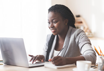 Smiling Black Businesswoman Working On Laptop And Taking Notes In Office.