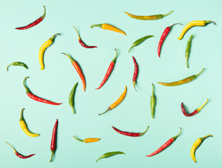 Red, green and yellow hot chili peppers in flat lay style texture. Pattern on neon mint background.