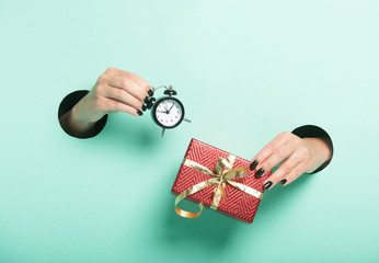 Female hands hold red gift and alarm clock through a hole on neon mint background. Isolated sale concept.