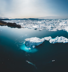 Iceberg and ice from glacier in arctic nature landscape in Ilulissat,Greenland. Aerial drone photo of icebergs in Ilulissat icefjord. Affected by climate change and global warming.