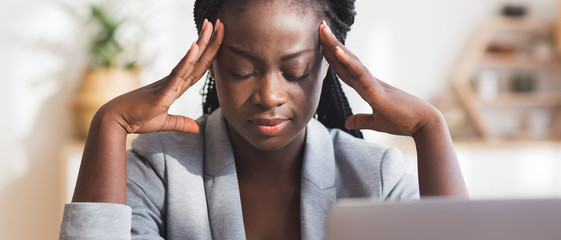 Tired black businesswoman suffering from migraine at workplace in office
