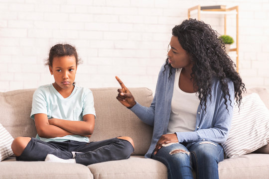 Grumpy black mother scolding her naughty little daughter on sofa at home