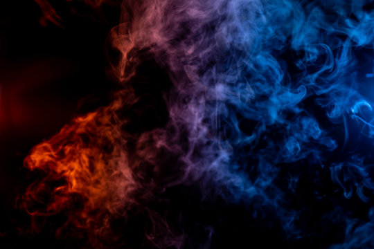 Whispy red purple and blue smoke in shape of a bear head on black background
