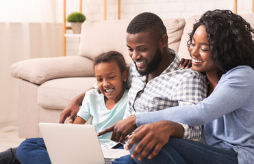 Joyful african american family using laptop at home together