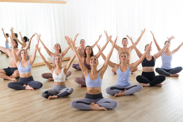 Fotomurales - Group of young sporty attractive people in yoga studio, practicing yoga lesson with instructor, sitting on floor in Padmasana, lotus meditative yoga pose. Healthy active lifestyle, working out in gym.