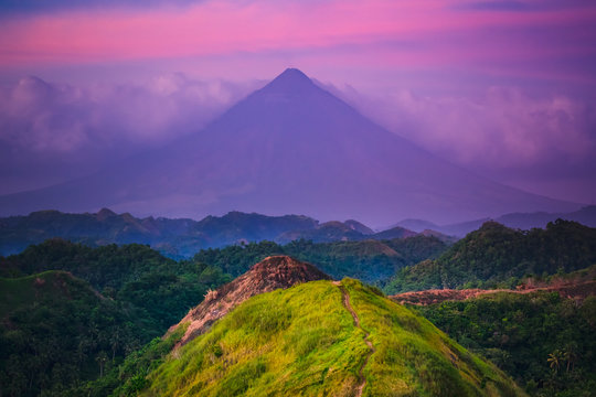 Sunset Mayon Volcano on Luzon Island Philippines. Wild Jungle Trees and Bushes, Mountain Peak and Cloudy Sky. Panoramic Photography on Amazing Exotic National Landscape View from Climb