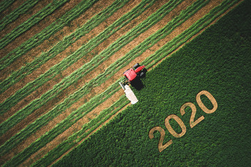 2020 Happy Ney Wear concept and red tractor mowing green field Fotomurales