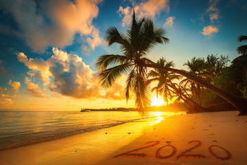 Happy New Year 2020 concept, lettering on the beach. Sea sunrise.