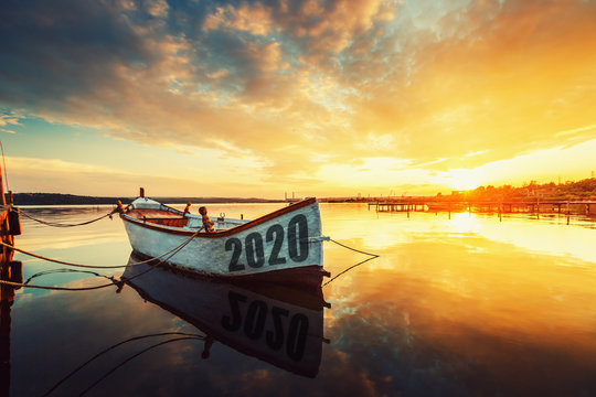 2020 concept Fishing Boat on Varna lake with a reflection in the water at sunset.