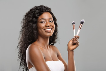 Fototapete - Beautiful black woman holding makeup brushes and smiling to camera