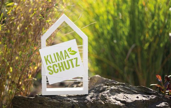 Weißes Haus vor natürlichen Hintergrund mit Schild Klimaschutz