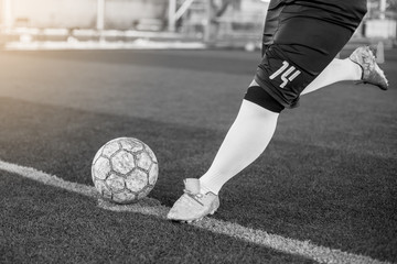 Black and white image of soccer player speed run to shoot ball to goal on artificial turf. Soccer player training for football match.