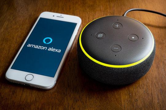 BATH, UK - DECEMBER 1, 2019 : Close up of an 3rd generation Amazon Echo Dot on a desk next to an Apple iPhone running the Amazon Alexa Application