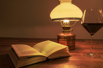 Old lamp on the wooden table with book and glass of wine