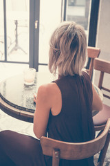 Toned picture of back view of beautiful blonde lady sitting in cafe or restaurant near window and looking through the window