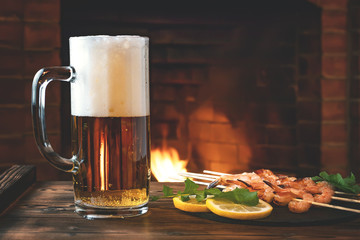 Mug of beer, fried on skewers of shrimp with arugula lemon on a black slate dish on a wooden table in room with a fireplace