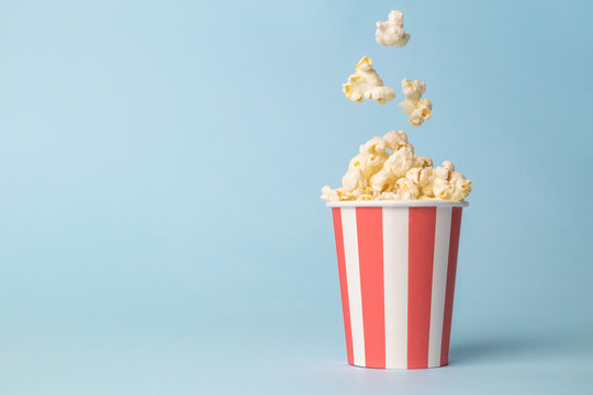 Falling popcorn in box isolated on blue.