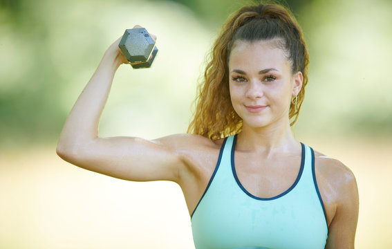 Beautiful young brunette woman (Caucasian) working out in park - lifting weight