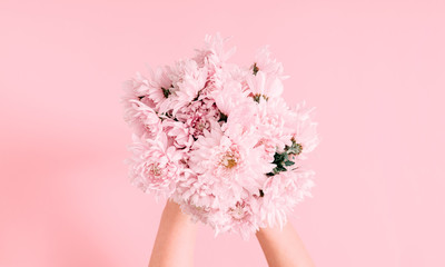 Beautiful flowers composition. Women's hand hold bouquet of pink light flowers on pastel pink background. Valentines Day, Mother's day. Flat lay, top view, copy space Fotobehang