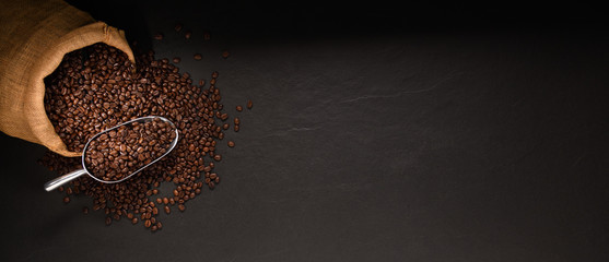 Coffee beans in burlap sack on black background