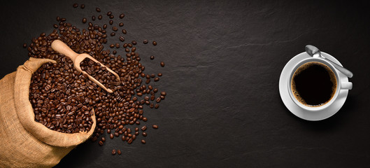 Coffee beans in burlap sack and cup of coffee on black background