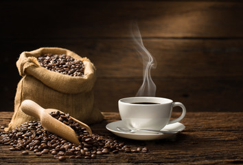 Aluminium Prints Cafe Cup of coffee with smoke and coffee beans on old wooden background