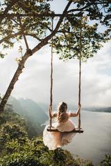 Rear view of woman in long white dress on swing in landscape