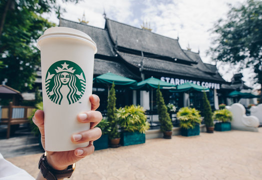 CHIANG MAI, THAILAND- July-24-2017 : Someone showing a cup of Venti size Starbucks hot coffee in front of of Starbucks Lanna style of Chiang Mai the northern province of Thailand.