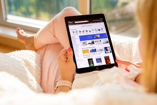 Riga, Latvia - July 21, 2018: Woman shopping for books on Amazon website on iPad.