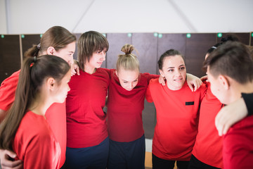 Large group of young sportswomen in red t-shirts standing in circle