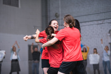 Ecstatic girls in sports uniform embracing after successful goal during game