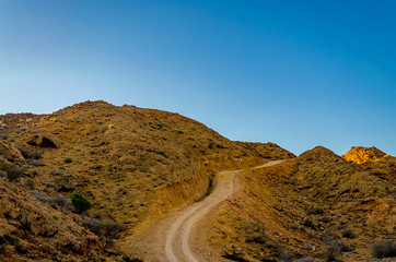 Winding dirt road through the orange colored barren mountains with a clear blue sky as background. From Muscat, Oman.