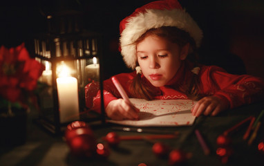 happy child girl writing letter santa home near Christmas tree.