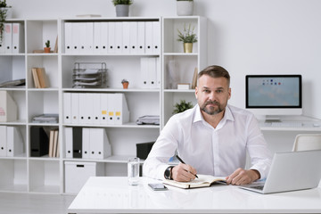 Confident employer in white shirt sitting in his office and organizing work
