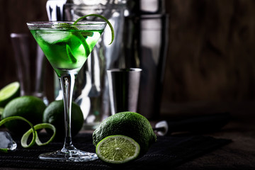 Green alcoholic cocktail martini glass with dry gin, vermouth, liquor, lime zest and ice, bar tools, dark background