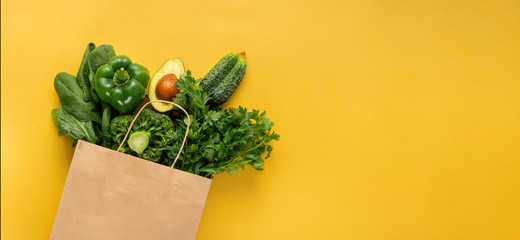 Shopping bag full green vegetables on yellow background with copy space  Purchase healthy food concept